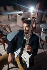 stylish bearded man with electric guitar;