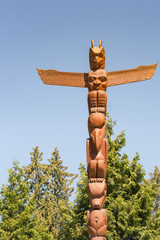 Vancouver, Canada - July 24, 2016: One of nine totem poles at Hallelujah point in Stanley Park. This one plain brown against blue sky. Green background.