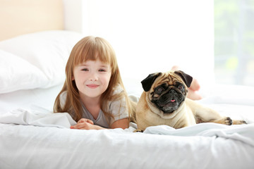 Beautiful girl and cute pug on bed