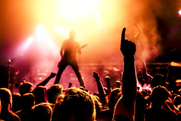 silhouette of guitar player in action on stage in front of concert crowd