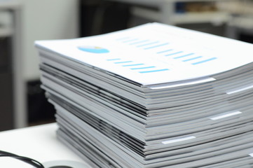 Stack of business reports on desk at workplace with high key tone.  - fototapety na wymiar