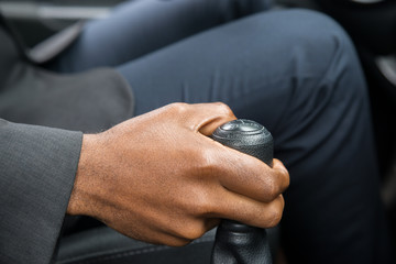 Person's Hand Changing Gear While Driving A Car