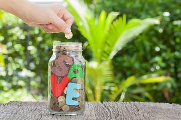 women hand putting money coin in jar. concept saving money  grow