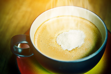 Creamer on top a cup of hot coffee.