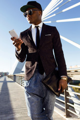 Handsome young black man using his mobile phone in the street.