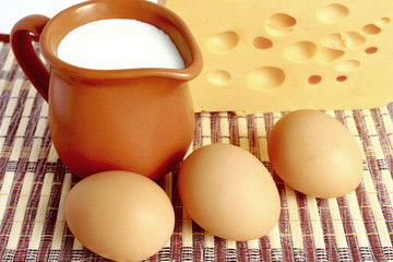 Milk, cheese and eggs on wicker background.