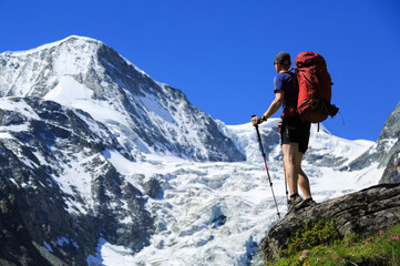 Hiker with backpack looking at mountain Pigne d' Arolla in Wallis, Switzerland, on a summers day.