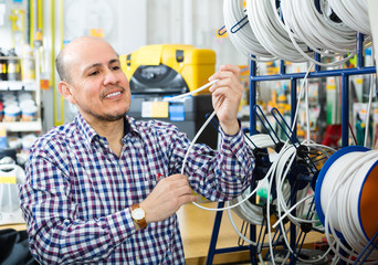 Man choosing cable in household store.