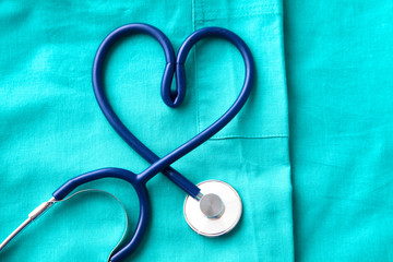 stethoscope shaping  heart and  clipboard on  medical uniform, closeup