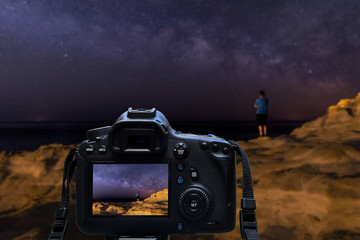 Camera shooting night sky at coast