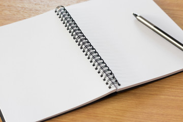 Blank notebook on the wooden desk background with a pen on top