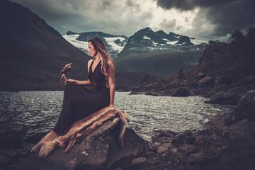 Nordic goddess in ritual garment with hawk near wild mountain lake in Innerdalen valley. Wall mural