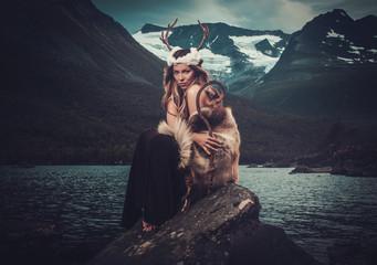 Nordic goddess in ritual garment near wild mountain lake in Innerdalen valley.