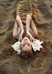 Mermaid with golden scales , huge pink shells and flowing hair lies on the sand in the late evening summer