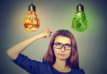 Woman thinking looking up at junk food and green vegetables light bulbs