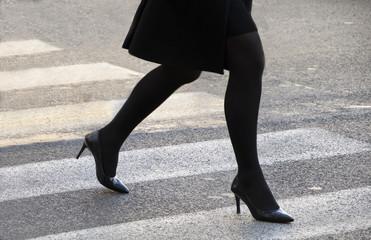 gambe di donna che attraversa le sulle strisce pedonali