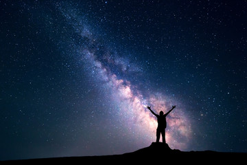 Landscape with colorful Milky Way. Night sky with stars and silhouette of a happy man with backpack and raised up arms on the stone. Space background