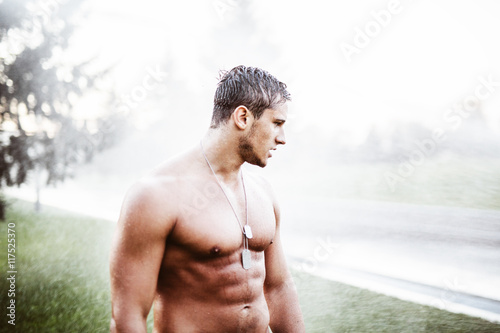 Man enjoying in the rain. young handsome guy with a naked