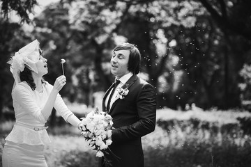 Black and white picture of a stylish bride blowing dandelion on