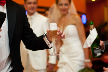 Man holds a glass full of champagne and foam