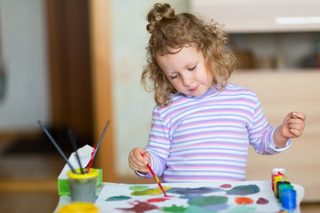 Little girl is drawing with paints.
