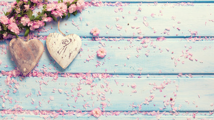 Pink sakura  flowers  and  two vintage decorative hearts on blue