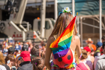 A female spectator with a rainbow flag is watching the gay pride