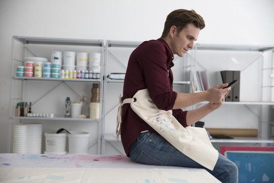 Man Working In Screen Printing Business Using Digital Tablet