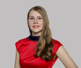 Young smiling woman  in red dress on a gray background isolated