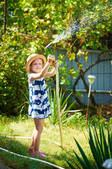 Little happy girl watering garden