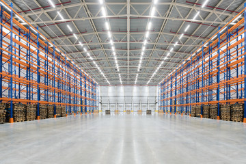 Empty huge distribution warehouse with high shelves and pallets