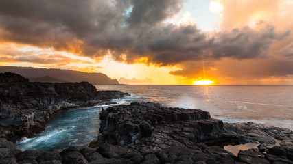 Man sitting on volcanic rock, Queens Bath, Kauai, Hawaii, United States of America