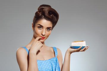 Picture of beautiful pin-up girl holding cake in hands at studio