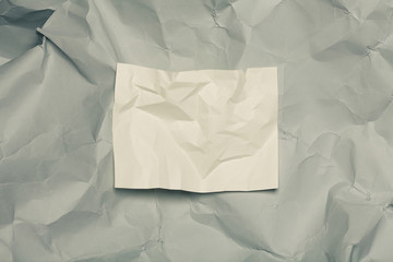 Modern art concept. Piece of white paper on gray crumpled one