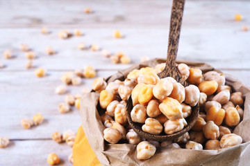 Dried chickpeas in a brown bag and a pile on a  wooden spoon.
