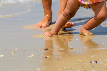 childrens and adults feet on the beach, a mother with  child, family