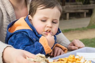 Kind ißt Curry Wurst mit Pommes friets