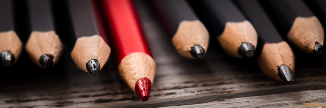 Red pencil stands out from the crowd of black  on a wooden white background.
