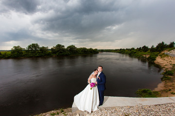 The bridegroom is embracing the bride on the river bank on a background of clouds