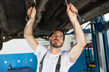 Mechanic works carefully on car