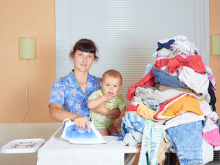 Mother holding baby in arm, ironing with the other arm.