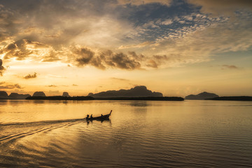 Silhouette scene of long-tail boat during morning sunrise in Phu