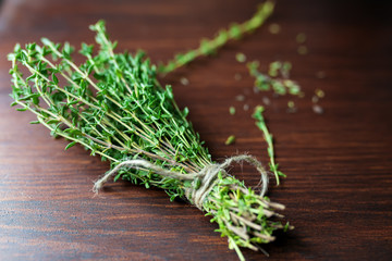 Fresh green bunch of thyme on wooden background