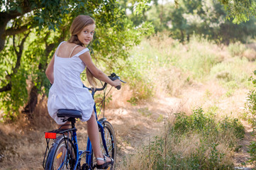 Cute girl child rides a bicycle to her grandmother in the village