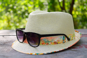 straw hat and sunglasses on a wooden table in a forest