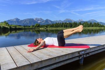 Frau bei Pilates-Übung auf einem Steg am See