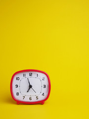 Red clock on yellow background.