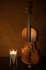 classical violins with  candle on old steel background
