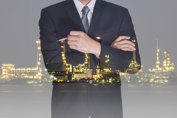 Double exposure of business man think idea and oil refinery industry plant in the night as Energy and Technology concept.