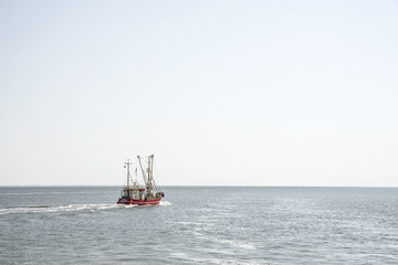 Roter Krabbenkutter verlässt bei stiller See den Hafen der Nordseeinsel Pellworm